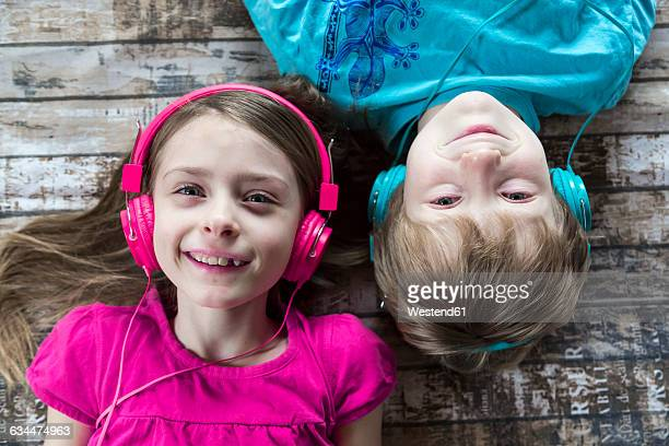Portrait of brother and little sister hearing music with headphones