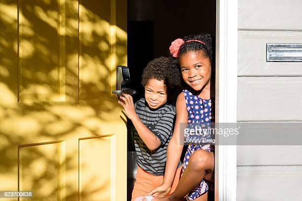 Portrait of brother and sister in doorway with sunlight