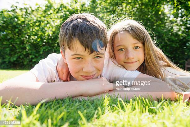 Portrait of brother and sister lying on grass