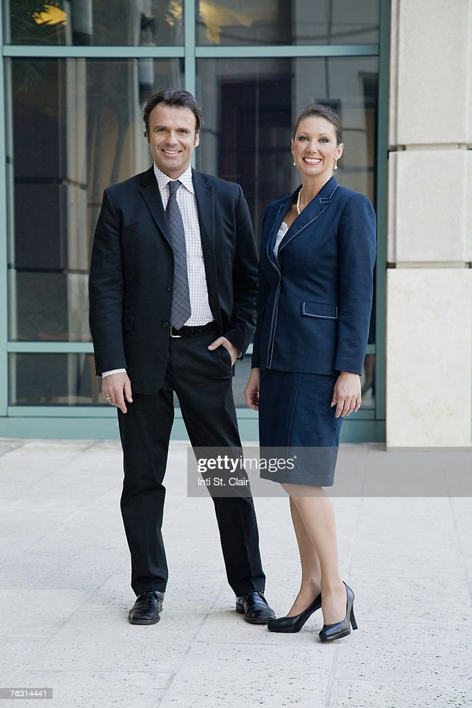 Portrait of business man and business woman outside building : Stock Photo
