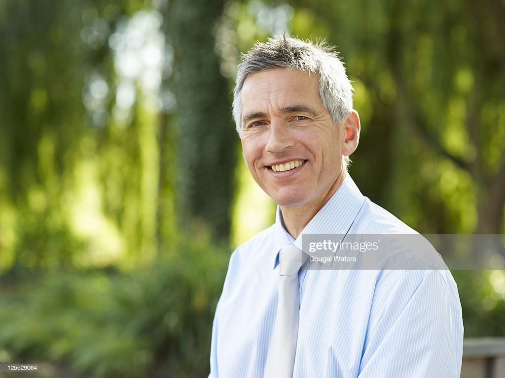 Portrait of business man in green space. : Stock Photo