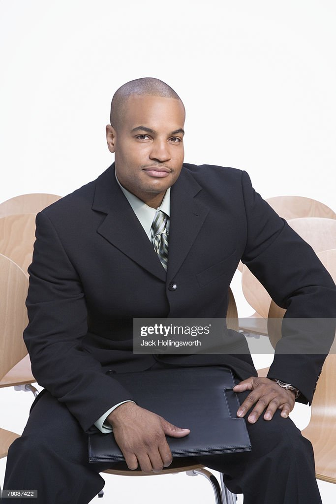 Portrait of business man sitting on chair, holding folder : Stock Photo