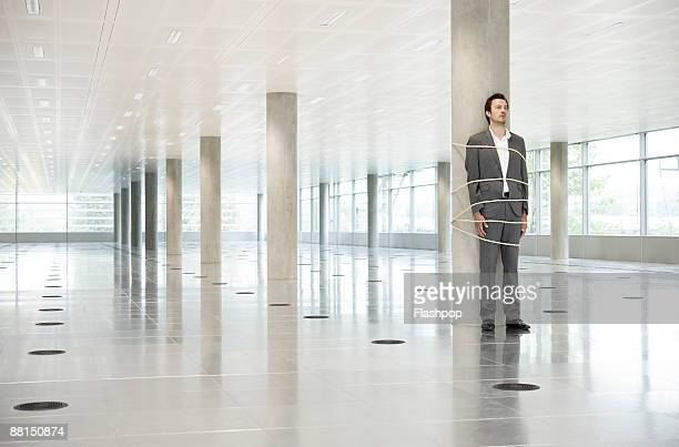Portrait of business man tied to pillar