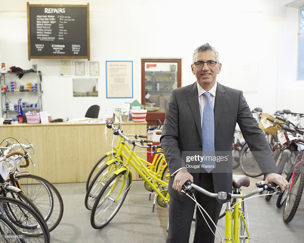 Portrait of business man with bicycle in shop. : Stock Photo