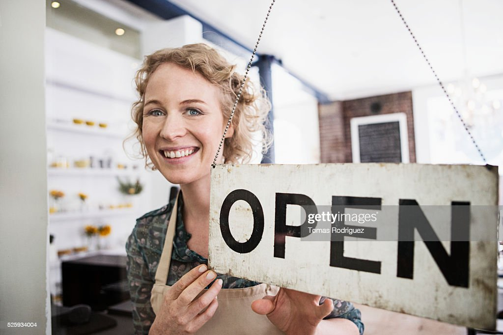 Portrait of business owner with open sign : Photo