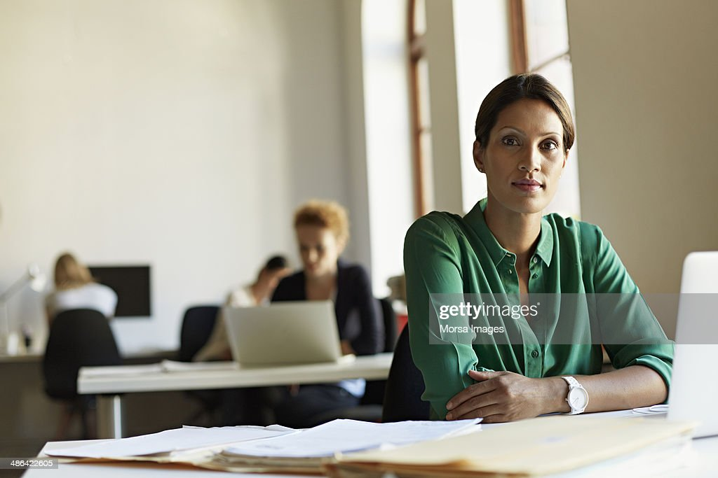 Portrait of business woman at work station : Stock Photo