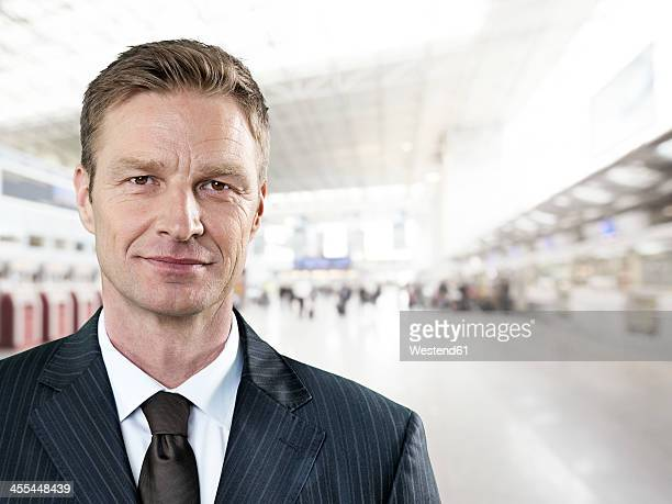 Portrait of businessman at airport, smiling