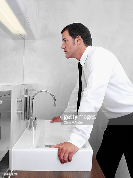 portrait of businessman checking his looks in mirror