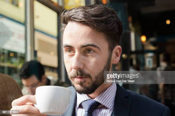 Portrait of businessman drinking coffee in urban cafe.