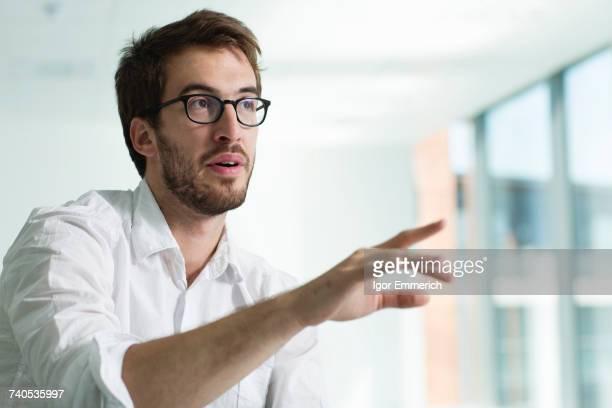 Portrait of businessman, hand raised in conversation