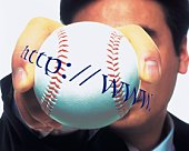 Portrait of businessman holding and raising a baseball with web site address, High Angle View, Close Up