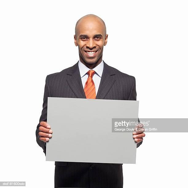Portrait of businessman holding blank card
