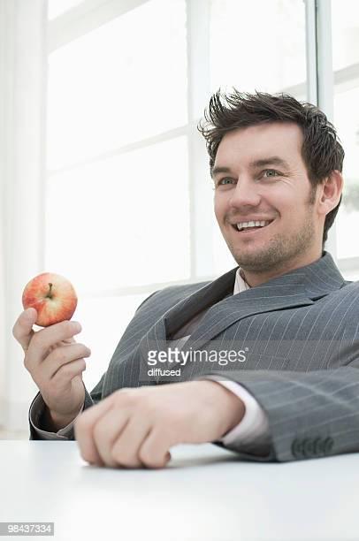 portrait of businessman holding red apple