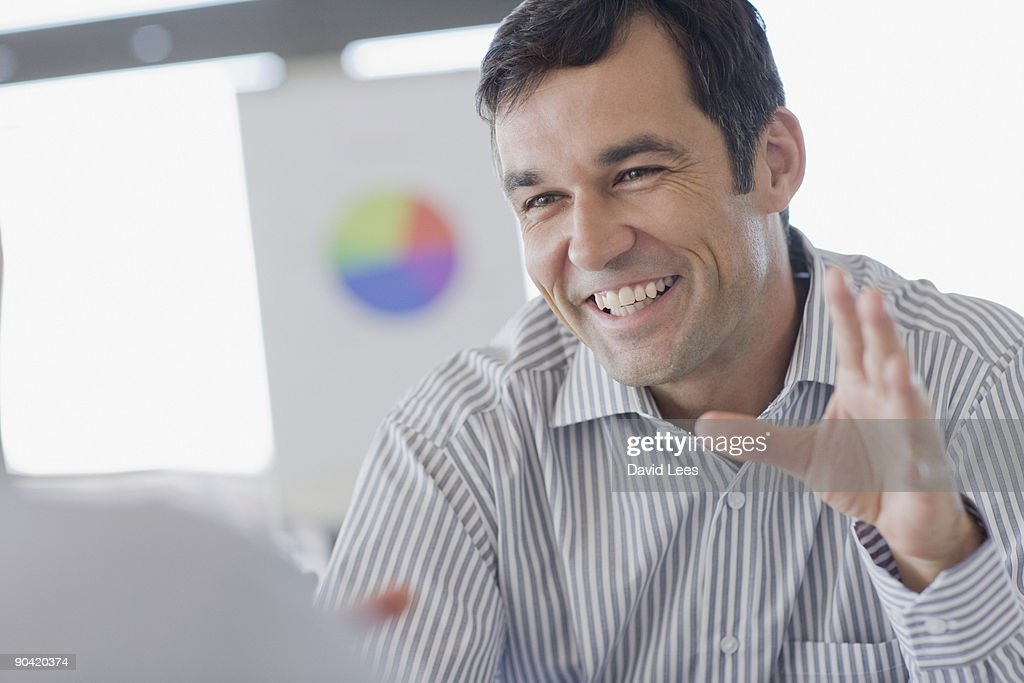 Portrait of businessman in meeting, smiling : Stock Photo