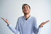 Portrait ofyoung Caucasian businessman wearing shirt standing, outstretching arms and laughing hysterically. Joy and humor concept