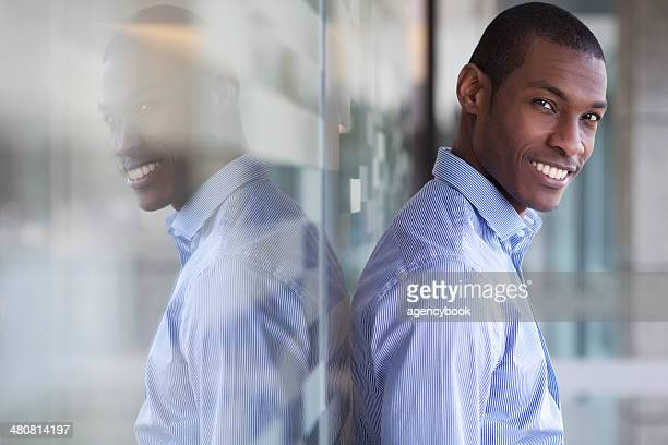 Portrait of businessman leaning against wall
