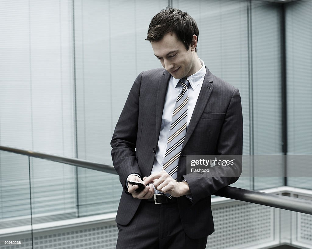 Portrait of businessman sending a message on phone : Stock Photo
