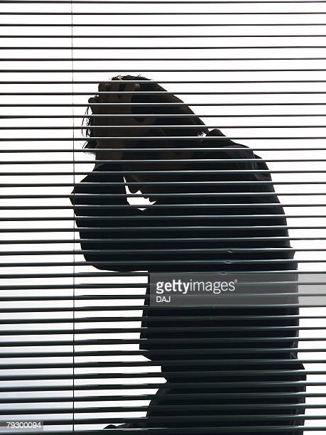 Portrait of businessman sitting and troubled by the blind, Side View, Silhouette