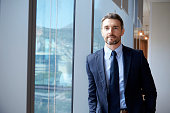 Portrait Of Businessman Standing By Window In Office