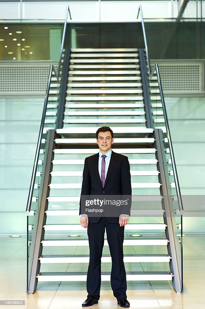 Portrait of businessman standing in modern office : Stock Photo