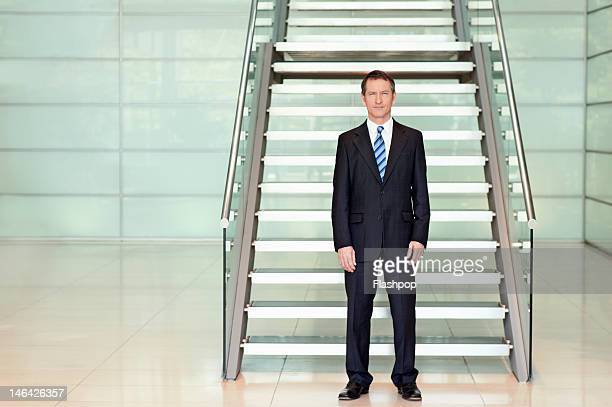 Portrait of businessman standing in modern office