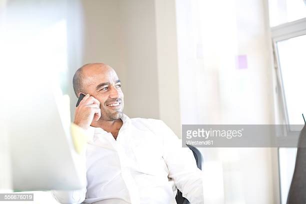 Portrait of businessman telephoning with smartphone at desk in an office