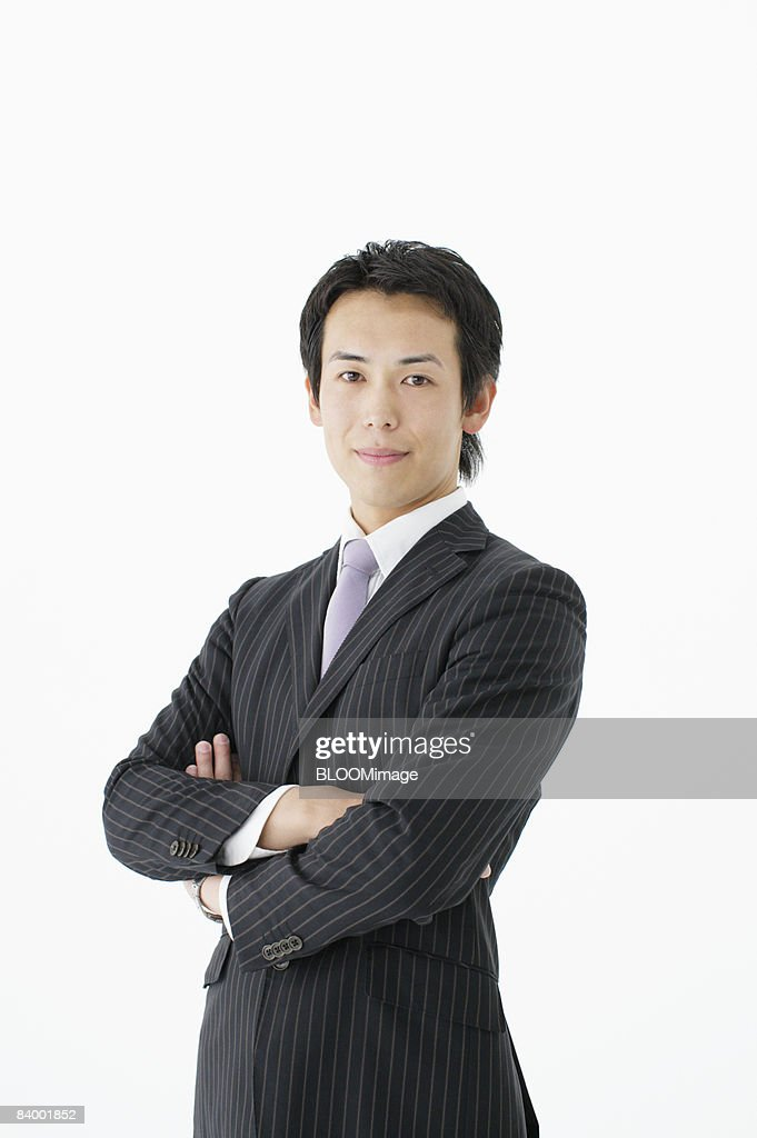 Portrait of businessman with arms folded, studio shot : Stock Photo