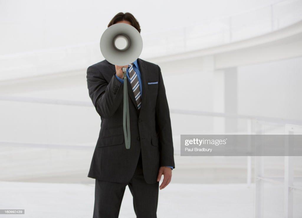 Portrait of businessman with bullhorn