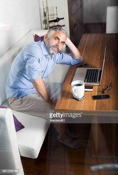 Portrait of businessman with laptop at his home office