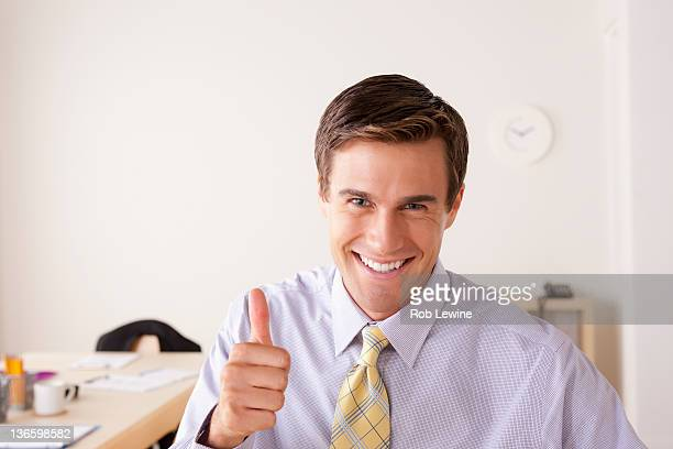 Portrait of businessman with thumbs up
