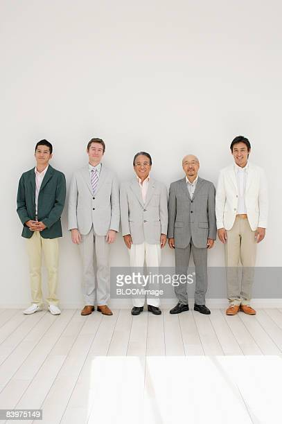 Portrait of businessmen standing in row against wall