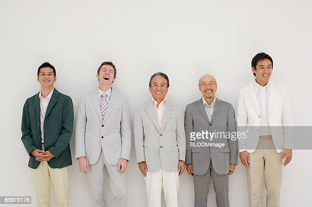 Portrait of businessmen standing in row against wall, smiling