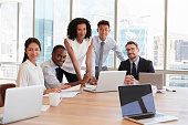 Portrait Of Businesspeople Meeting Around Table In Office