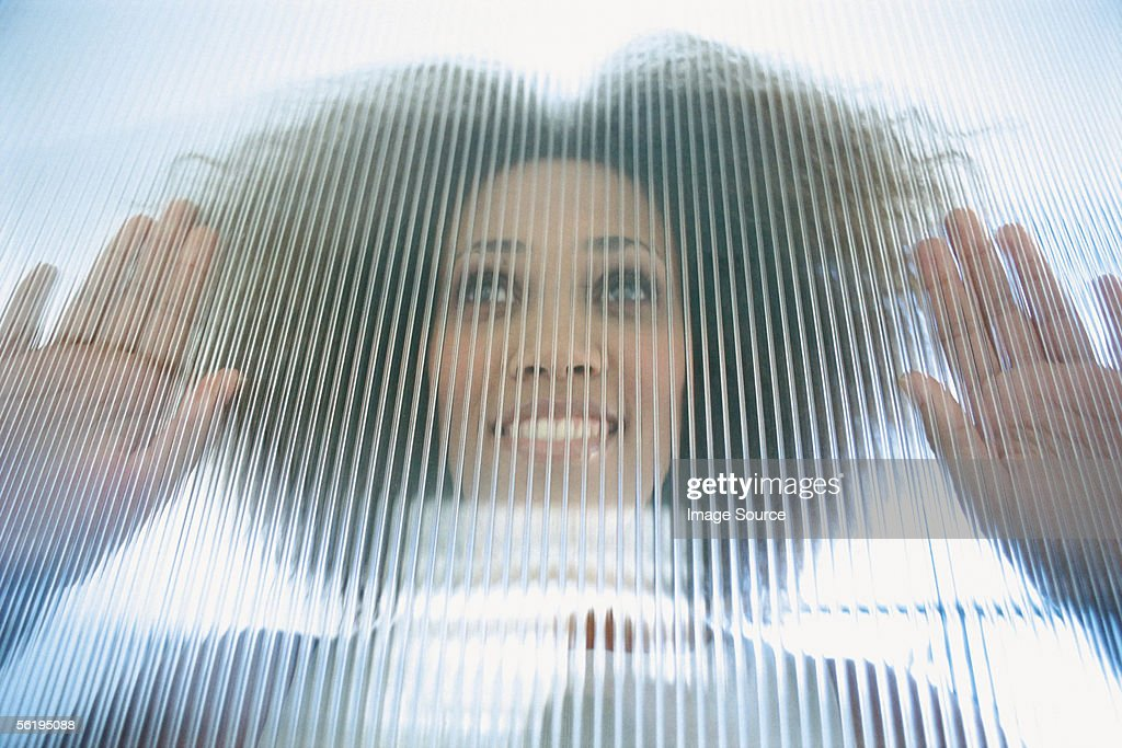 Portrait of businesswoman behind a glass screen : Stock Photo