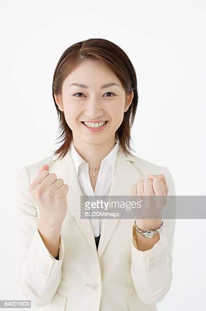 Portrait of businesswoman clenching fists, studio shot