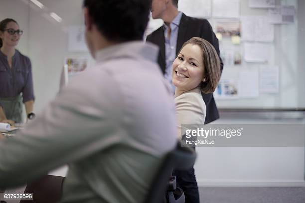 Portrait of businesswoman in busy planning meeting with colleagues