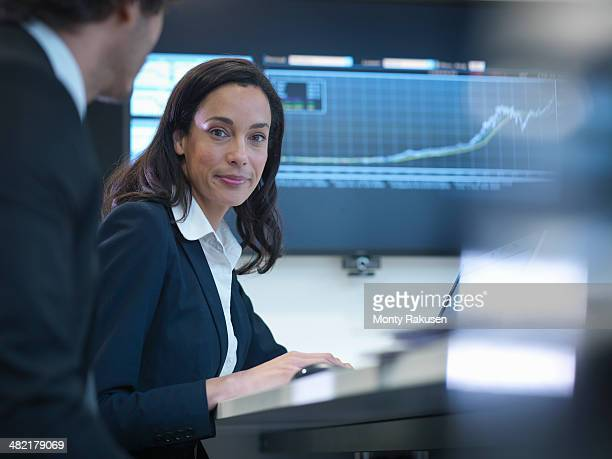 Portrait of businesswoman in meeting in front of screen in office