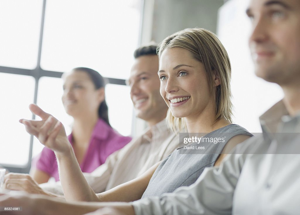 Portrait of businesswoman in meeting, smiling : Stock Photo