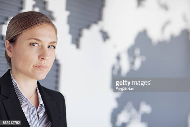 Portrait of businesswoman in room with map on wall