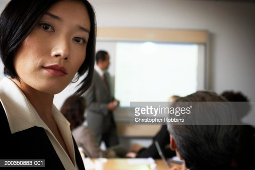 Portrait of businesswoman, man by projection screen in background
