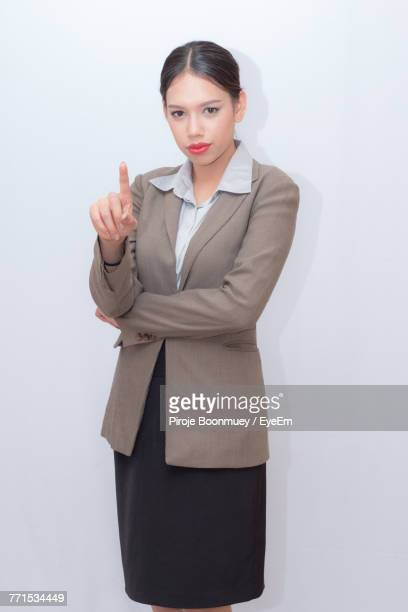 Portrait Of Businesswoman Pointing Against White Background