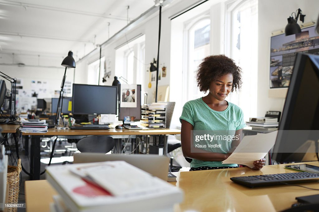 Portrait of businesswoman reading a paper : Stock Photo