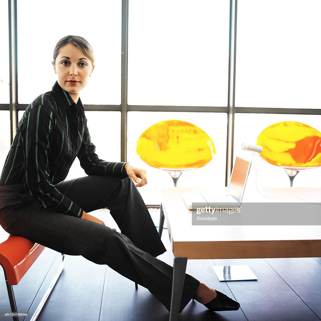 portrait of businesswoman sitting on the edge of a chair in front of a laptop : Stock Photo