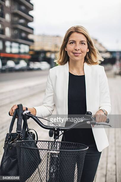 Portrait of businesswoman standing with bicycle in city