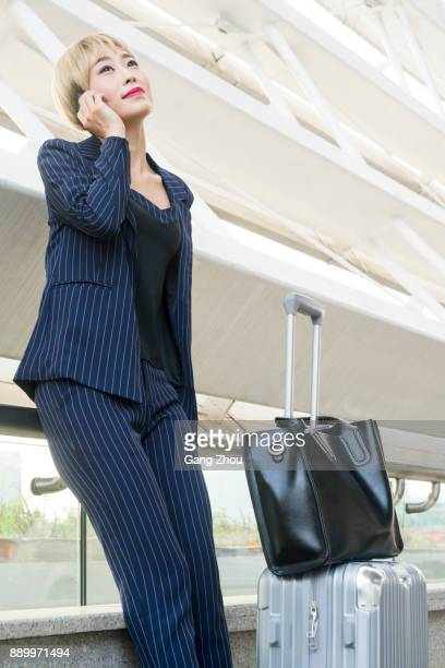 portrait of businesswoman talking on phone with suitcase in airport/station