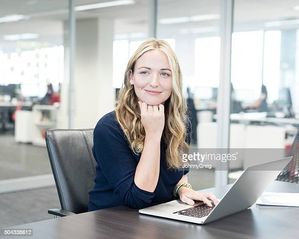 Portrait of businesswoman using laptop with hand on chin