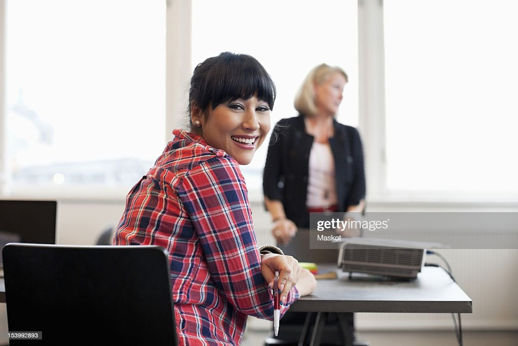 Portrait of businesswoman with colleague in the background : Stock Photo