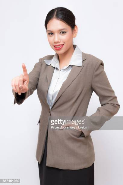 Portrait Of Businesswoman With Hand In Pocket Pointing Against White Background