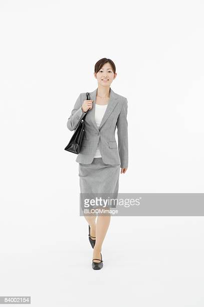 Portrait of businesswoman with shoulder bag, studio shot