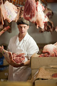 Portrait of butcher holding raw meat
